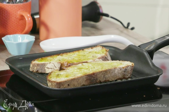 Полить ломти хлеба небольшим количеством оливкового масла и обжарить на сковороде гриль до легкой золотистой корочки.
