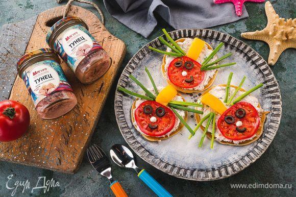 Выложите в центр тарелки блинчик. Из кружка помидора сделайте голову, которую дополните глазками и ртом из маслины. Из ломтика болгарского перца сделайте спинку жука, а из зеленого лука — лапки. Приятного аппетита!
