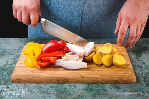 Тем временем картофель разрежьте пополам, лук, болгарский перец и рыбу нарежьте крупно.
