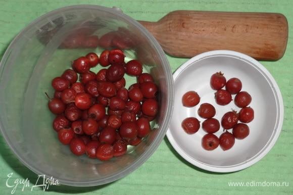 Небольшую часть ягод отложить, остальные ягоды боярышника помять деревянным пестиком.