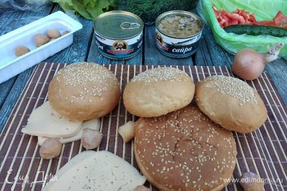 Подготовим ингредиенты: булочки разрезать на 2 части, сыр — на пластины, моем перец, укроп, листья салата. Нижние булочки я полила немного соусом из-под рыбы. Первый слой на булочку выложить сыр.