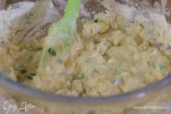 В отдельной посуде соединить поленту со сметаной, сахаром и яйцами, влить 120 мл оливкового масла и перемешать все в однородную массу, затем всыпать кукурузу, порезанный лук и перемешать.