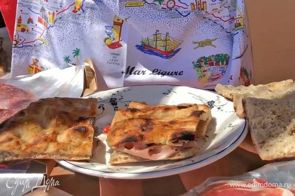 Накрыть бутерброд верхней частью фокаччи и разрезать пополам.