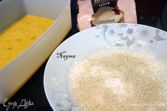 В глубокую миску разбить три яйца. Взбить их венчиком или вилкой. На тарелку насыпать муку, добавить кунжут и перемешать.