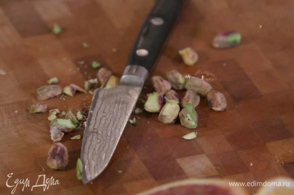 Фисташки порубить ножом и посыпать рыбу.