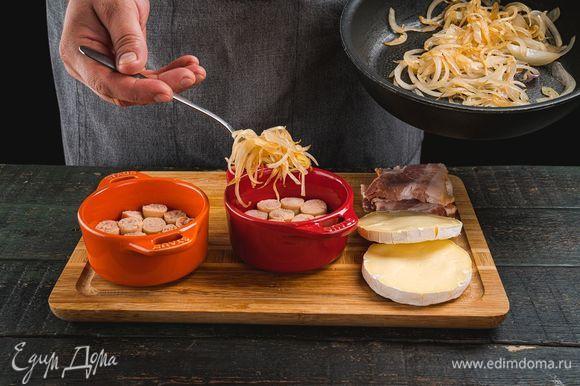 В форму для запекания выложите нарезанные кружочками колбаски «По-французски» ТМ «Петруха Мастер». Сверху добавьте обжаренный лук и чеснок.