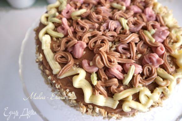 Нанести орехи (50 г) на бока торта. Оформить верх торта c помощью кондитерского шприца кремом разных цветов, можно использовать цукаты.