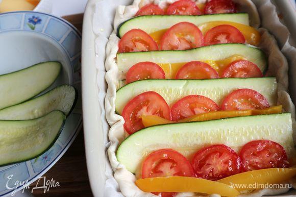 Сверху поместить овощи, чередуя пластины цукини, полоски желтого болгарского перца, колечки помидоров. Размещать таким образом, чтобы одна часть овощей заходила на другую. Смазать кисточкой бортики из теста взбитым яйцом. Отправить в духовку на 40 минут.