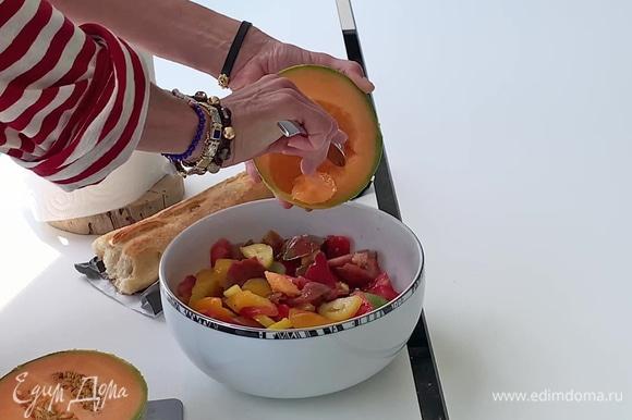 Дыню разрезать пополам, удалить семечки. С помощью ложки вынуть мякоть и добавить в салат.