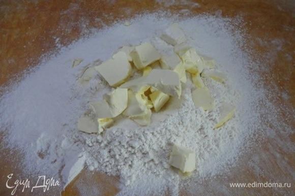 Муку просеять на рабочую поверхность. Сделать небольшое углубление, всыпать в него сахарный песок, соль и сливочное масло кусочками. Порубить с помощью ножа до состояния крошки.