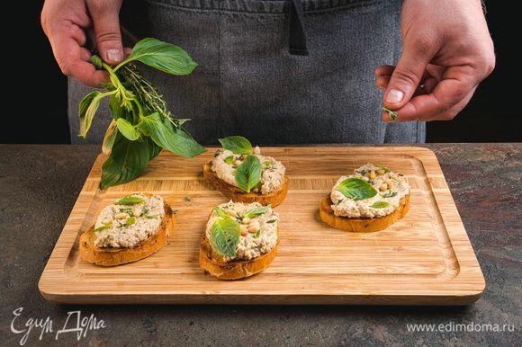 Выложите тапенаду на зерновой хлеб, украсьте поджаренными кедровыми орехами, базиликом и тимьяном.