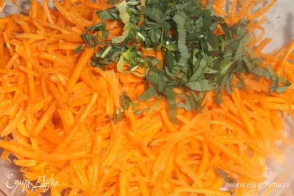 Морковь натереть на терке для корейской моркови. Посолить. Слегка помять. Добавить нарезанные листья. Перемешать. Добавить растительное масло. Накрыть салатник крышкой. Дать настояться в течение часа.