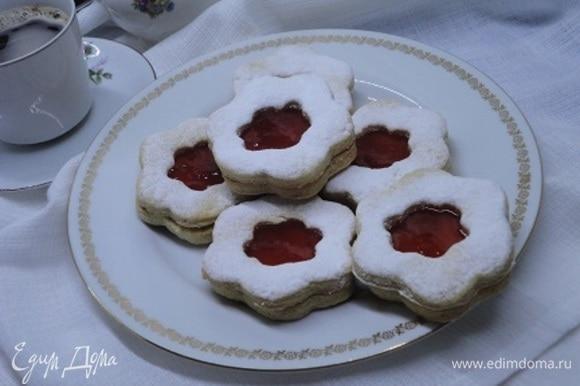 Остывшее печенье соедините попарно, предварительно смазав клубничным или малиновым вареньем (а можно использовать абрикосовый кофитюр или даже тонкий слой масляного крема).