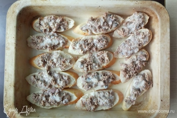 Тонкий батон (багет) нарезать кусочками толщиной 1 см (10–12 кусочков), уложить на противень. На батон распределить получившуюся начинку.