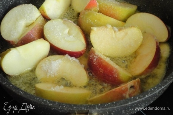Яблоки вымыть, разрезать каждое на 8 долек и удалить сердцевину с семенами. На сковороде растопить оставшееся сливочное масло, положить туда яблоки, посыпать сахаром и при постоянном помешивании жарить на сильном огне 10 минут.