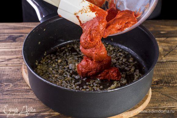 Добавьте пасту к луку с чесноком. Получившийся соус доведите до кипения.