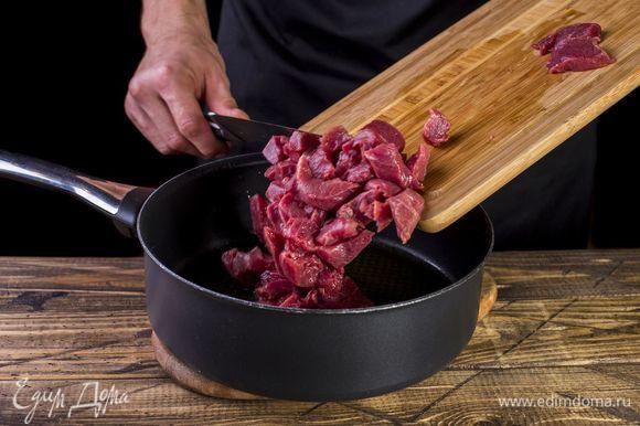 Говядину нарежьте брусочками и обжарьте в сотейнике на растительном масле до появления корочки.