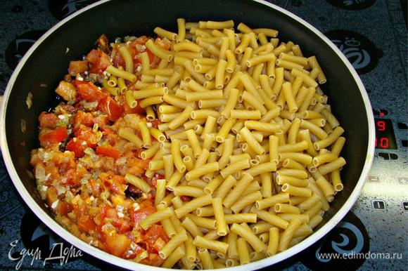 К обжаренным овощам всыпать пачку макарон (450–500 г), посолить и поперчить по вкусу.