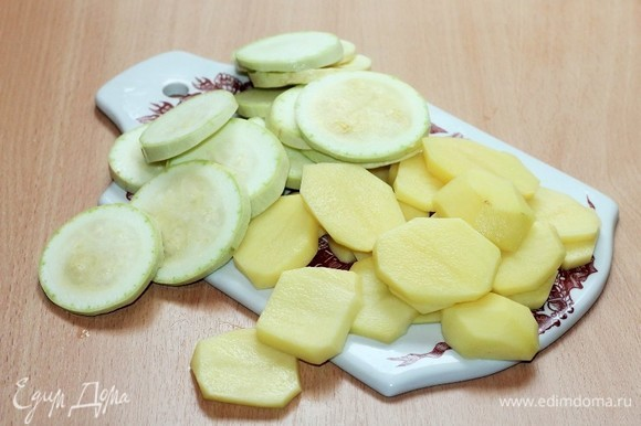 Картофель очищаем. Кабачок и картофель нарезаем кружочками и бланшируем в кипящей подсоленной воде до полуготовности.