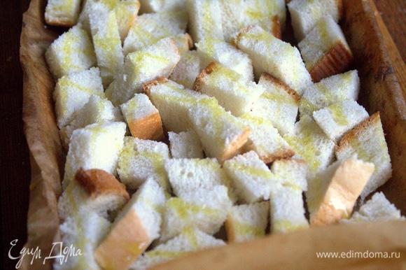 Обычный батон нарезать кубиками, сбрызнуть оливковым маслом.