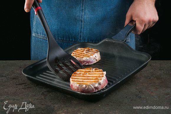 Посыпьте медальоны солью, перцем. Обжарьте медальоны на сковороде-гриль по 3–4 минуты с каждой стороны.