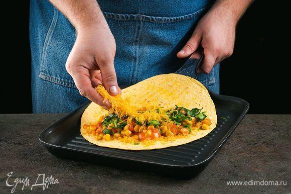 Выложите на одну половинку лепешки обжаренные овощи с креветками, мелко нарезанную петрушку. Сверху посыпьте тертым сыром.