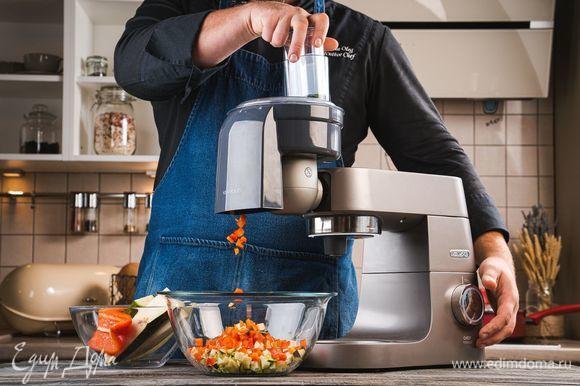 Промойте все овощи и обсушите бумажными полотенцами. Установите на кухонную машину KENWOOD насадку для нарезки кубиками. С ее помощью нарежьте баклажан, болгарский перец и цукини.