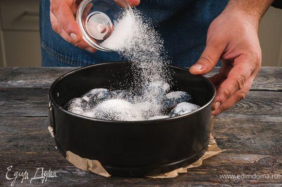 Форму для выпекания смажьте сливочным маслом, выложите ровным слоем сливы и посыпьте сахаром.