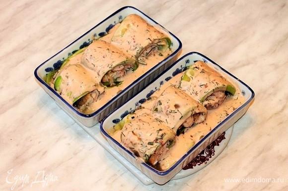 Полить кабачковые рулеты сверху соусом и отправить в разогретую до 180°C духовку на 30 минут. Затем кладем на рулетики пластины сыра и половинки помидорчиков черри, посыпаем обжаренным кунжутом. Ставим формочки в духовку до расплавления сыра на 1–2 минуты.