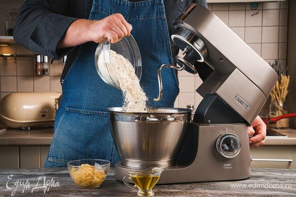 В чашу кухонной машины добавьте лук и 1 ст. л. оливкового масла. С помощью насадки для смешивания хорошо перемешайте ингредиенты. Далее используйте насадку крюк, чтобы замешать тесто. Постепенно добавляйте муку, чтобы получилось мягкое, слегка прилипающее к рукам тесто и замесите тесто с помощью насадки крюк. Поставьте тесто на расстойку в теплое место на 1 час.