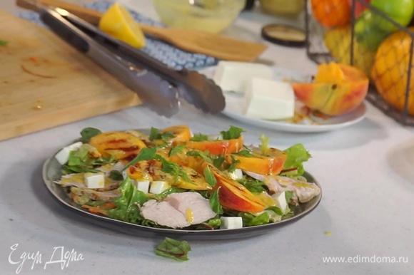 На блюдо выложить салатный микс с заправкой, добавить кусочки индейки и нарезанную кубиками фету. Сверху положить запеченные на гриле персики. Полить салат оставшейся заправкой и посыпать листочками мяты.
