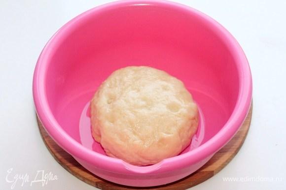 Собираем тесто в ком. Смазываем миску растительным маслом (1 ч. л.) и выкладываем тесто. Прокручиваем тесто в масле. Накрываем миску пленкой, чтобы тесто не обветрилось.