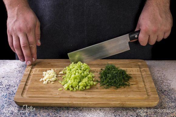 Подготовьте соус. Огурец помойте, снимите с него кожуру и мелко нарежьте. Чеснок и укроп мелко порубите.