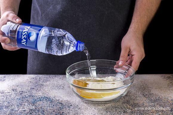 Добавьте к тесту газированную воду Tassay. Замесите упругое и эластичное тесто. Накройте тесто пищевой пленкой и оставьте на 20 минут.