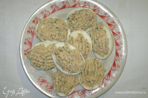 Нафаршировать яйца начинкой. С помощью вилки сделать узоры. Поставить яйца в холодильник для охлаждения.
