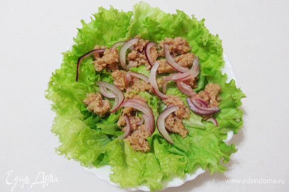 Салатные листья порционно разложить по тарелкам. Сверху положить кусочки консервированного тунца и маринованный лук.