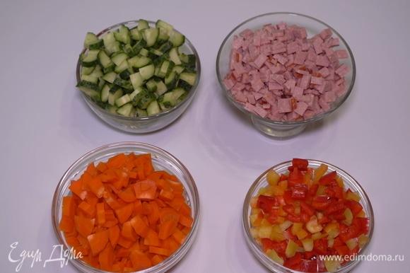 Нарезаем кубиками огурцы, отварную морковь, сладкий перец и колбасу.