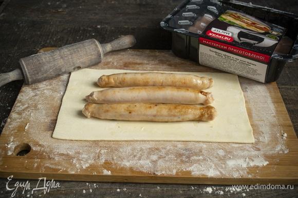 На неразрезанный лист теста кладем остывшие колбаски, нужно по 3 штуки на 1 пирожок.