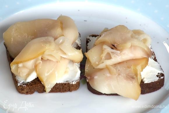 На хлеб намазать сливочный сыр, сверху выложить рыбу.