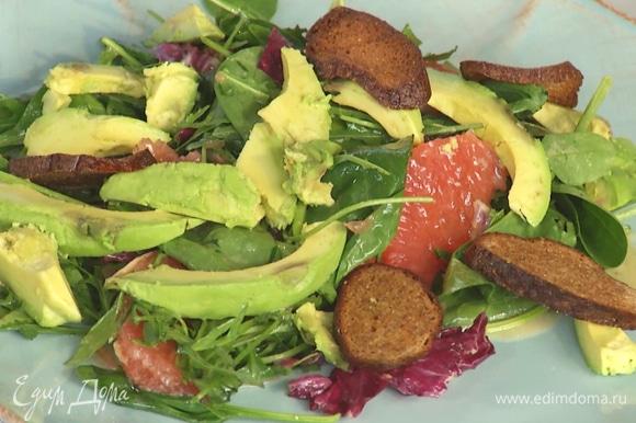 На тарелку выложить салат. Сверху положить авокадо и крутоны.