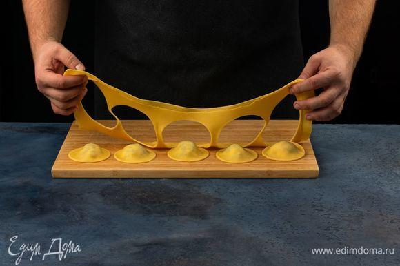 Накройте второй половиной теста, скрепите края и разрежьте стаканом на кружочки. В подсоленную кипящую воду добавьте веточку розмарина и равиоли. Отварите равиоли до готовности.