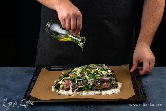 Противень застелите пергаментной бумагой, распределите небольшое количество солевой массы, выложите мясо, слегка брызните оливковым маслом.