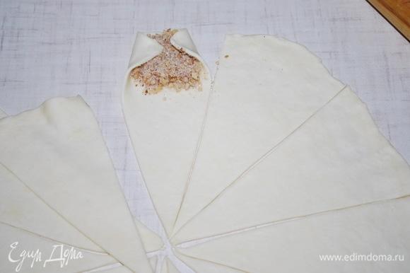 Тесто разрежьте на треугольники, положите начинку и подверните края теста, чтобы при заворачивании рулетика начинка была закрыта.