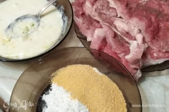 Мясо нарезать на порционные куски примерно по 100 г. Отбить с двух сторон. Посолить, поперчить. Сметану смешать с яйцом. Добавить измельченный чеснок. Муку смешать с панировочными сухарями.