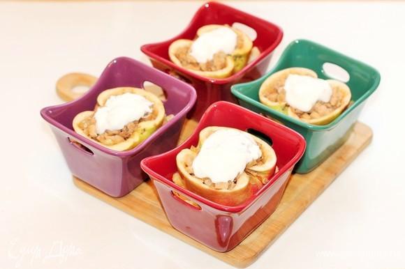 Добавляем по 1 ст. л. сметаны. Накрываем формочки фольгой и отправляем в разогретую до 180°C духовку. Запекаем до мягкости яблока, около 30–45 минут.