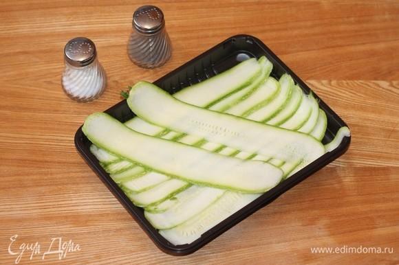 Кабачки разрезаем по всей длине на пластины толщиной в 5–7 мм и солим. Оставляем на 15 минут в сторону. Включаем духовку нагреваться до 180°C.