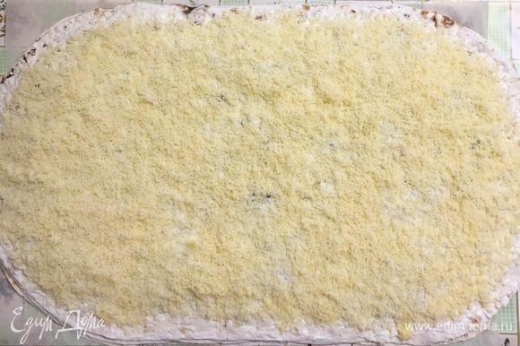 Четвертый лаваш смазываем соусом и посыпаем сыром по всей поверхности.