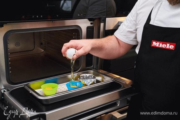 Сварите яйца-пашот. Для этого разбейте каждое яйцо и поместите отдельно в силиконовую формочку для кекса. Накройте фольгой и готовьте на пару в пароварке с СВЧ 4 минуты.
