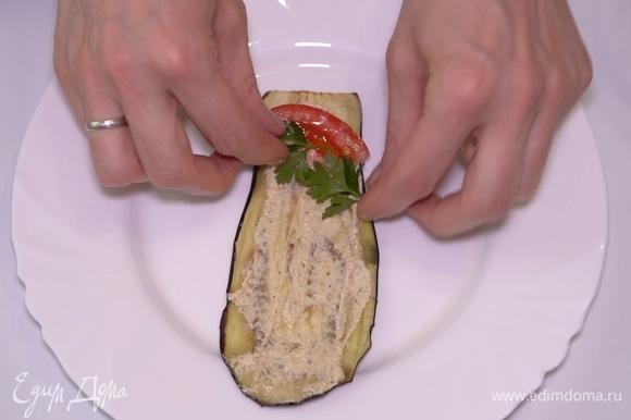 Выкладываю на остывшую баклажанную пластинку 1 ч. л. начинки. Кладу сюда кусочек помидора и веточку петушки. Аккуратно сворачиваю рулетиком.