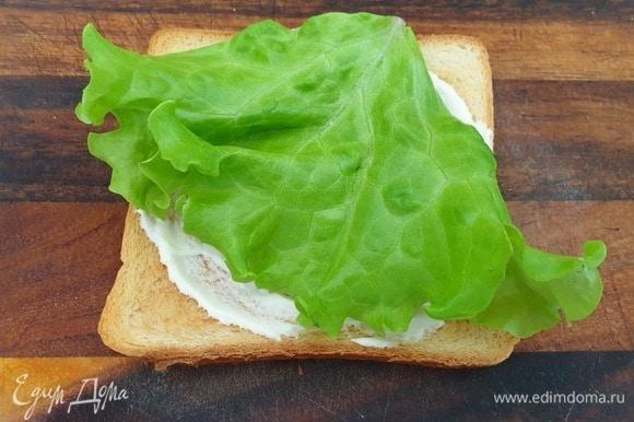 Хлеб смазываем майонезно-горчичным соусом, кладем лист салата.
